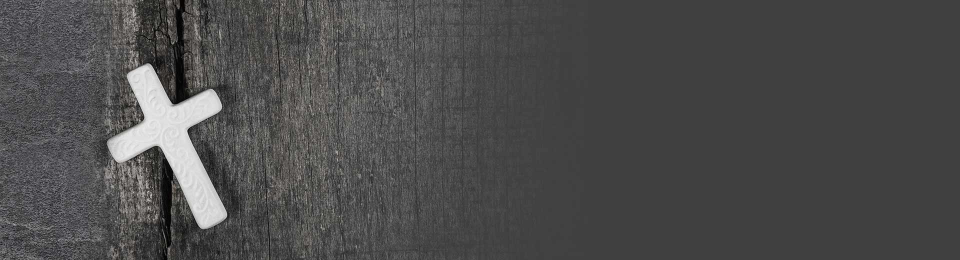 Weisses Kreuz vor schwarzer Holzwand