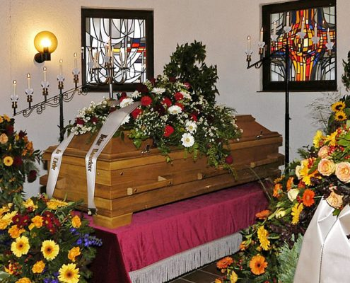 Blumengeschmückter Sarg in Kirche aufgebahrt
