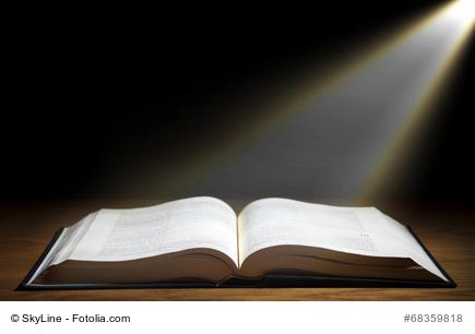 Lichtstrahlen fallen auf ein aufgeschlagenes Buch